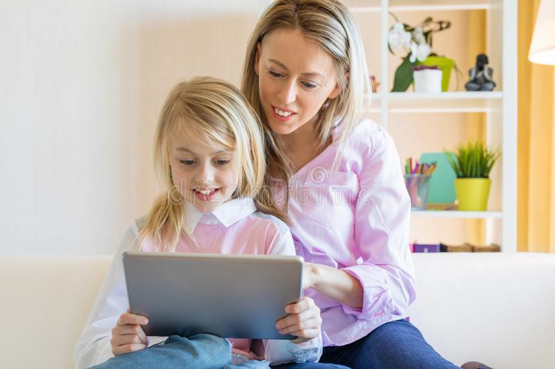 Blonde cheerful girl with her mother using tablet computer together royalty free stock photography
