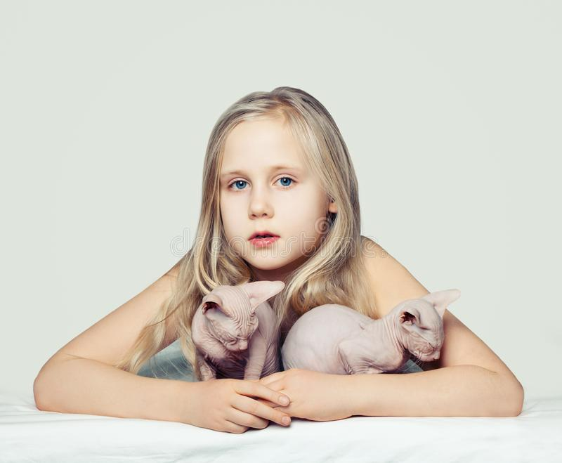 Blonde child girl and kittens. Child with 2 pets stock photo