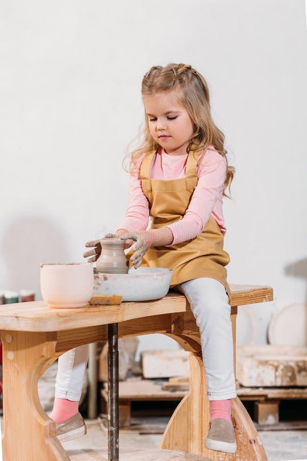 blonde child making ceramic pot on pottery wheel stock images