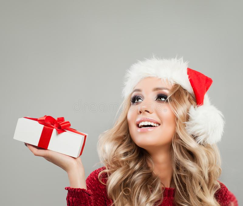 Blonde Christmas Woman with White Christmas Gift Box Looking Up. Perfect Model in Santa Hat on Gray Background royalty free stock images