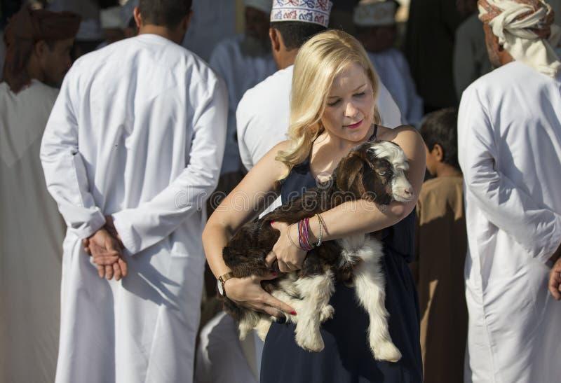 Blonde con una cabra del bebé en el mercado del hábito en Nizwa fotos de archivo
