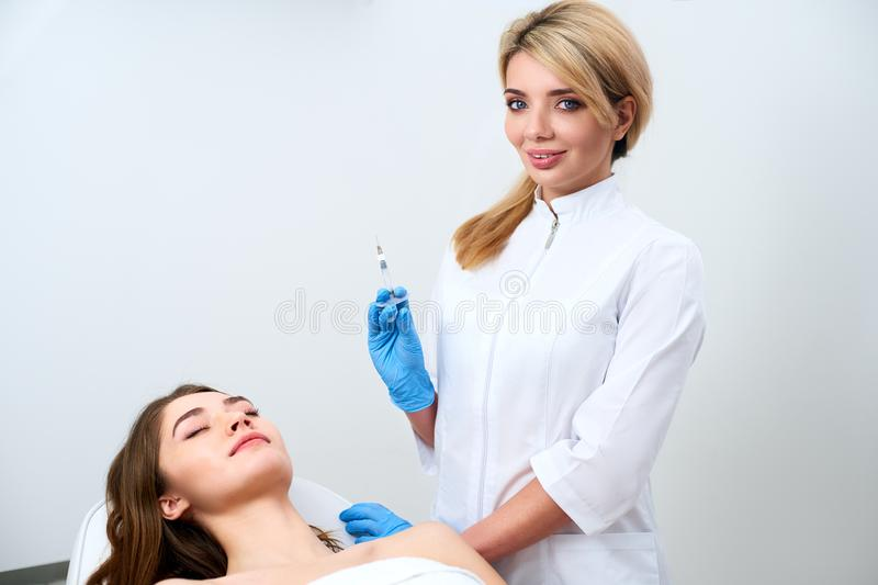 Cosmetologist doctor standing near patient and holding botulinum syringe wearing gloves before operation, injections royalty free stock images