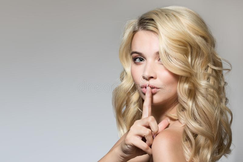 Blonde with curls on a gray background stock images