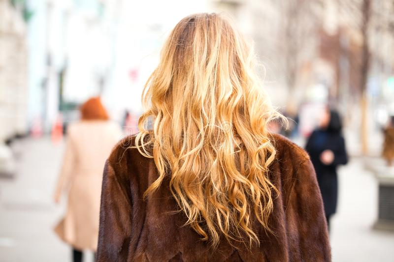 Blonde curly in fur coat walking autumn street. Healthy Wavy hair. Back view royalty free stock images