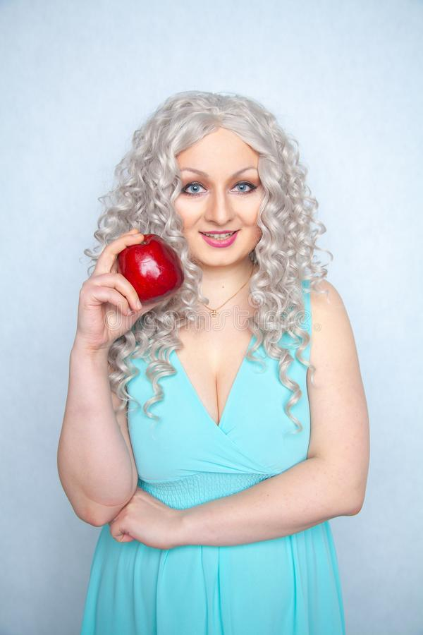 Blonde curly girl in blue dress holding tasty big red apple and smile on white studio solid background royalty free stock photos