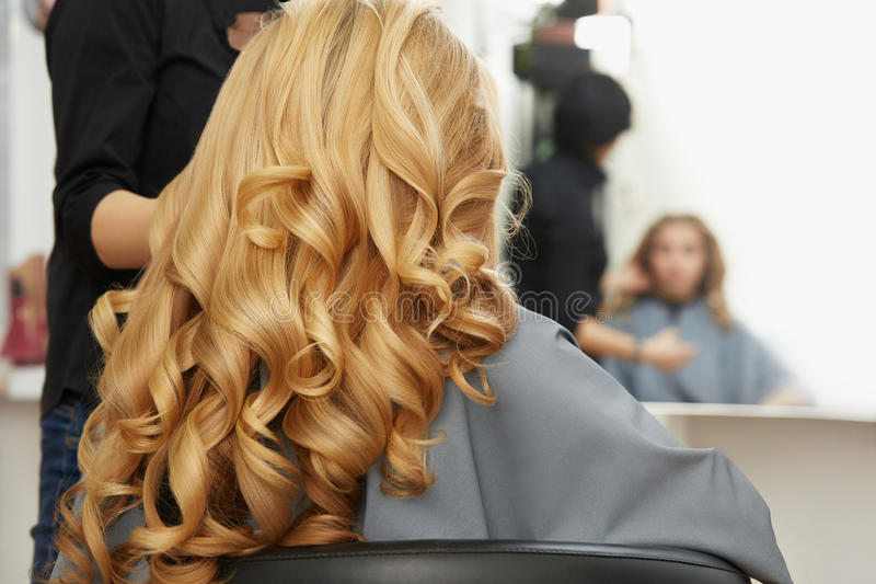 Blonde curly hair. Hairdresser doing hairstyle for young woman i stock image