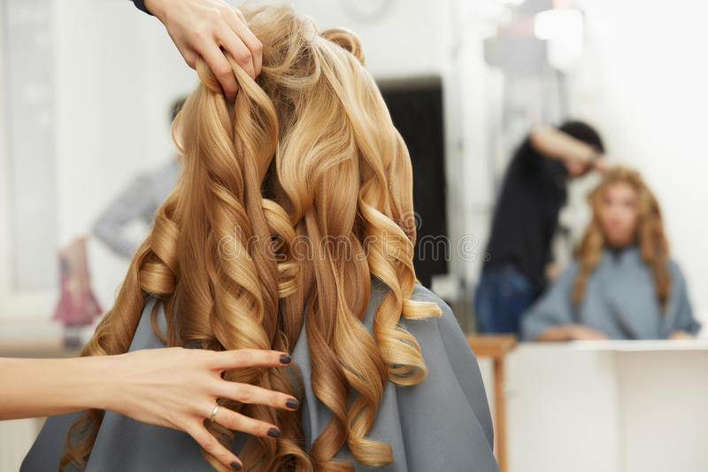 Blonde curly hair. Hairdresser doing hairstyle for young woman i stock images