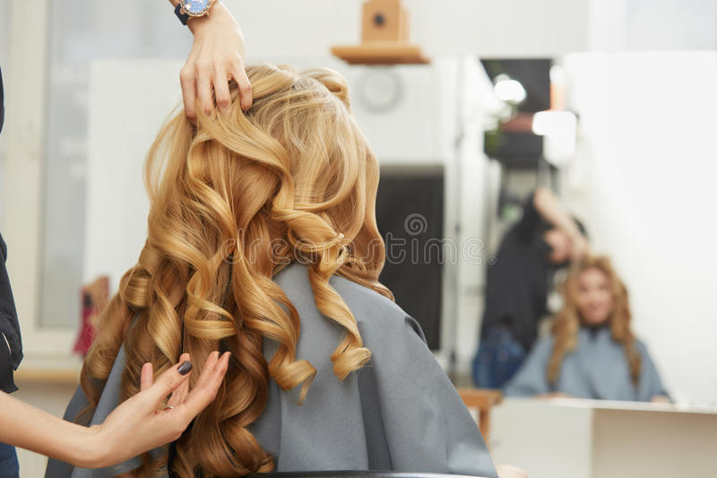 Blonde curly hair. Hairdresser doing hairstyle for young woman i royalty free stock photo