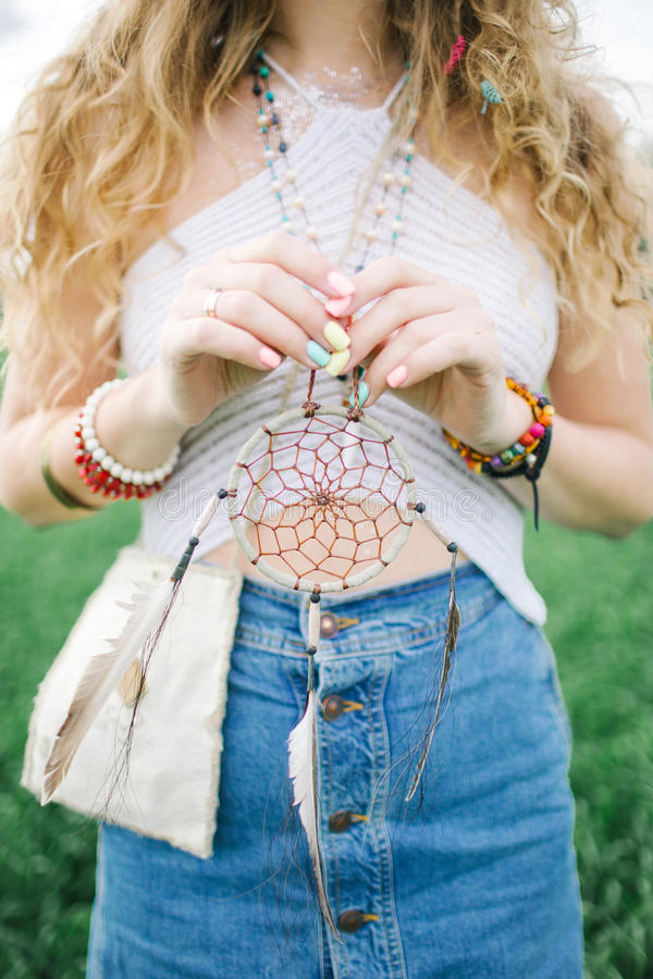 Blonde curly hippie woman with dream catcher in hands royalty free stock photo