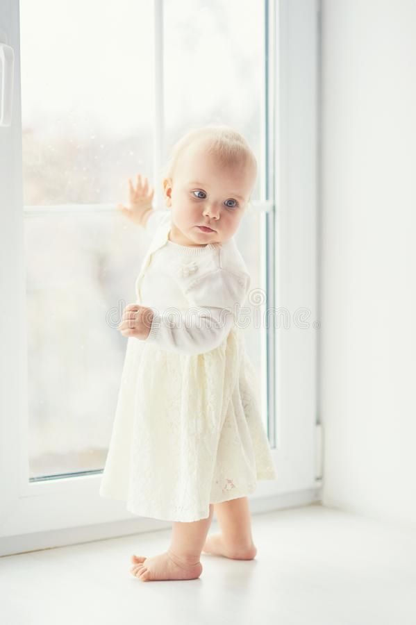 blonde curly toddler Baby girl looking through a window royalty free stock photos