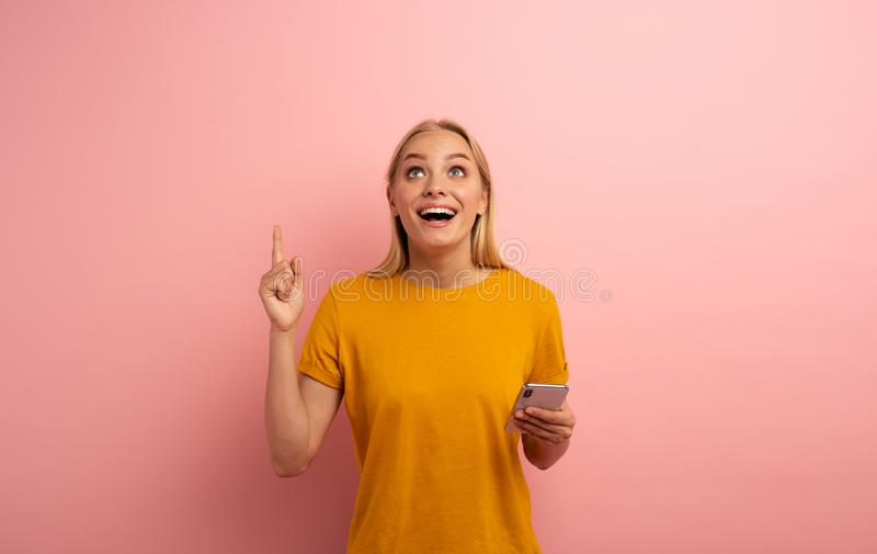 Blonde cute girl, with her smartphone, indicates something. Amazed and surprised expression face. Pink background with royalty free stock image