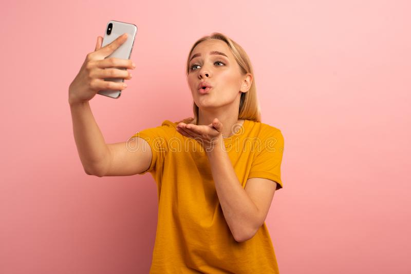 Blonde cute girl sends hearts on her smartphone. Happy and lovely expression face. Pink background stock images