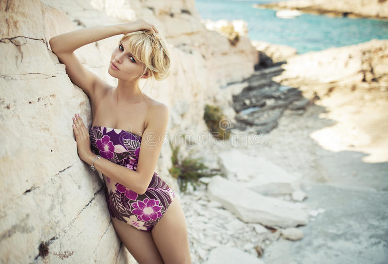 Blonde cutie leaning on the bright rock royalty free stock photo