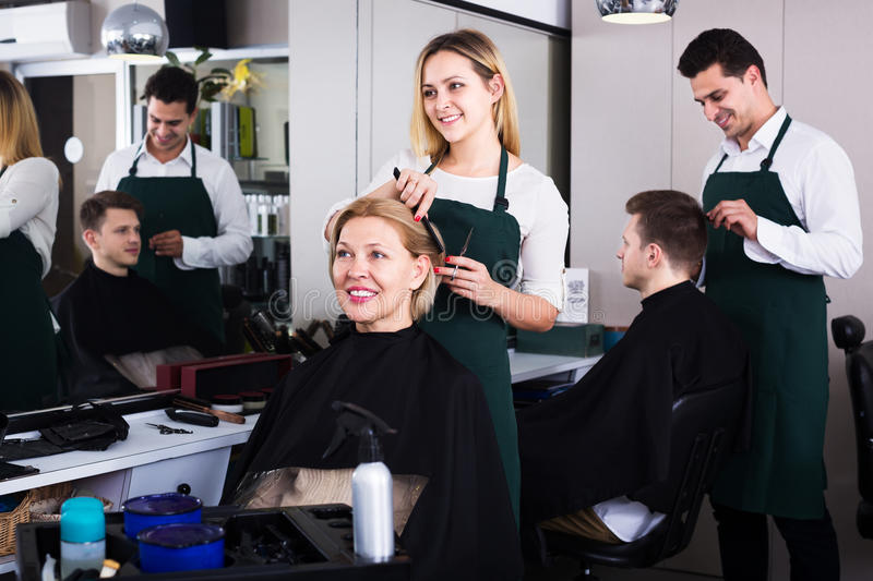 Blonde cuts hair at salon. Positive blonde cuts hair of mature women at salon royalty free stock images
