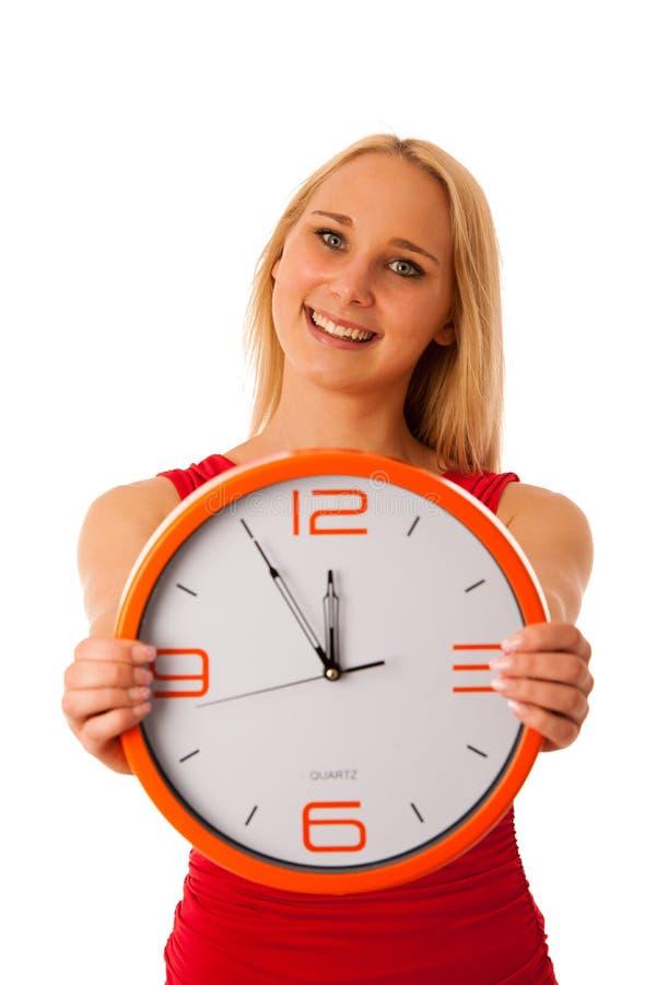 Blonde de bedrijfsvrouw in rood overhemd houdt klok als teken voor tijd stock foto's