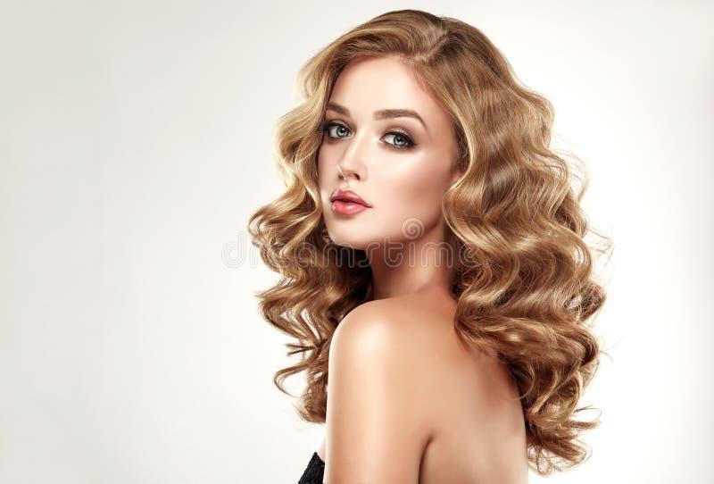 Blonde de femme avec la coiffure volumineuse, brillante, bouclée et lâche photographie stock