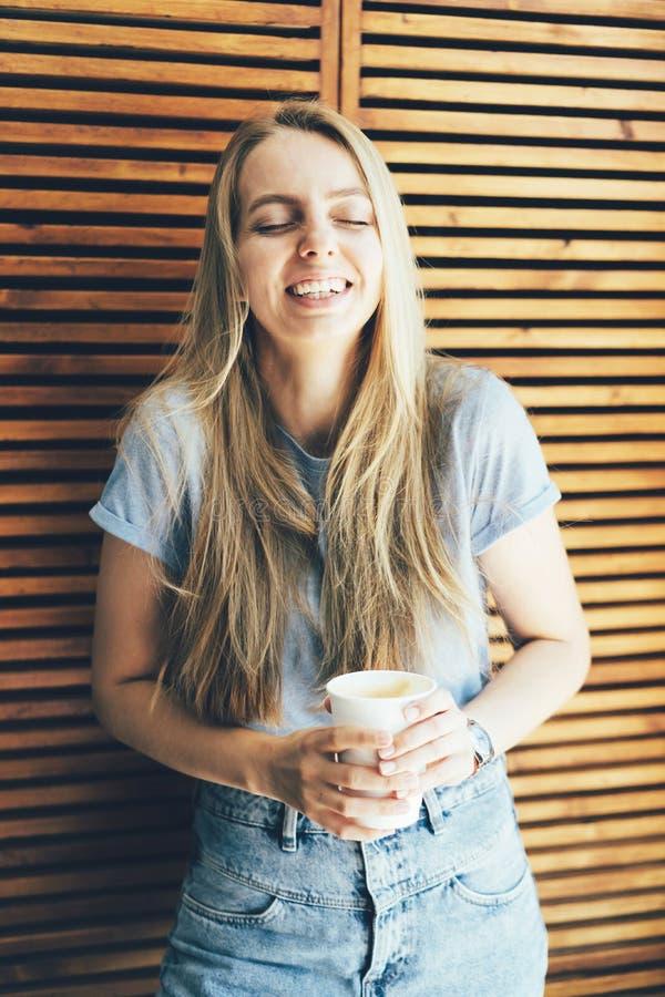 Blonde de hippie d'étudiante avec de longs rires de cheveux d'une plaisanterie d'amusement photos libres de droits