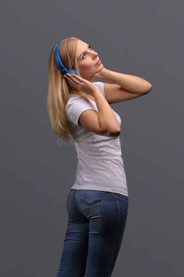 Blonde de jeune fille dans des écouteurs bleus Écoutant, appréciant la musique Isolat sur un fond gris photographie stock