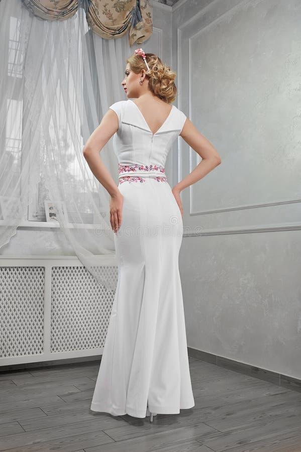 Blonde de la mujer elegante, hermosa, de moda en un dre blanco largo fotografía de archivo