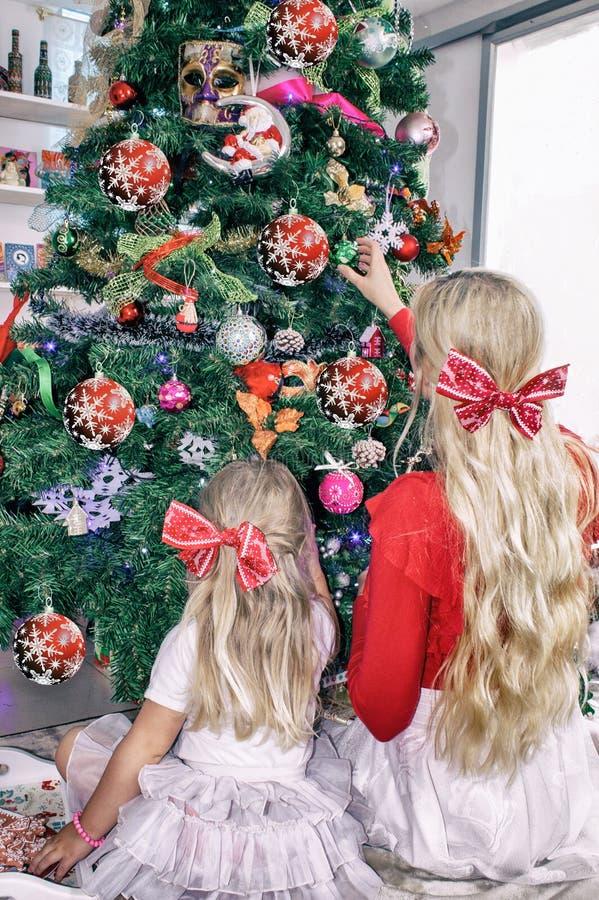 Blonde de maman et de fille avec des arcs, se reposant au sapin de Noël et le décorer photos stock