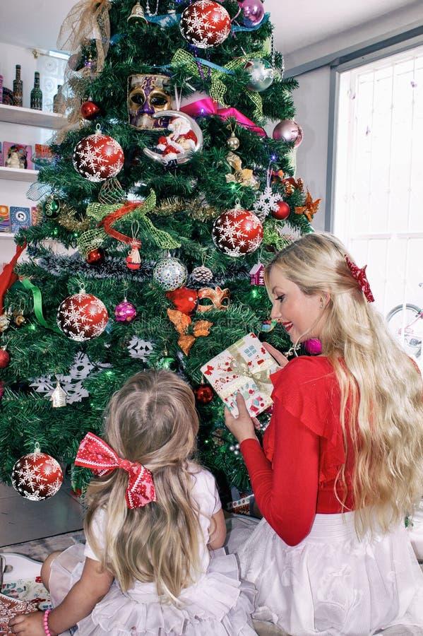 Blonde de maman et de fille avec des arcs, se reposant au sapin de Noël et le décorer images stock