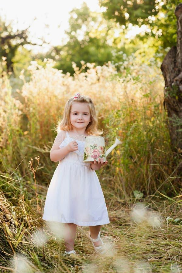 Blonde de petite fille dans une robe blanche dans le jardin avec de l'eau, riant, enfance, relaxation, sérénité photo libre de droits