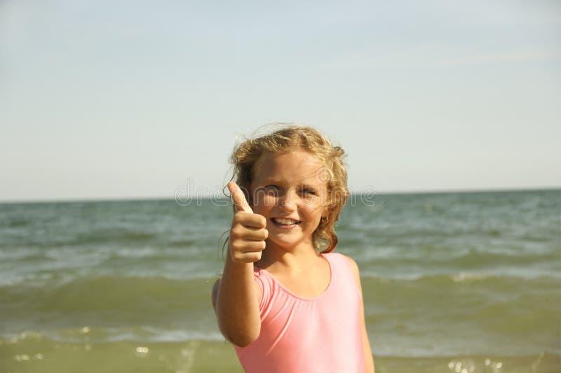blonde de petite fille sur le sable de plage, classe de signe images stock