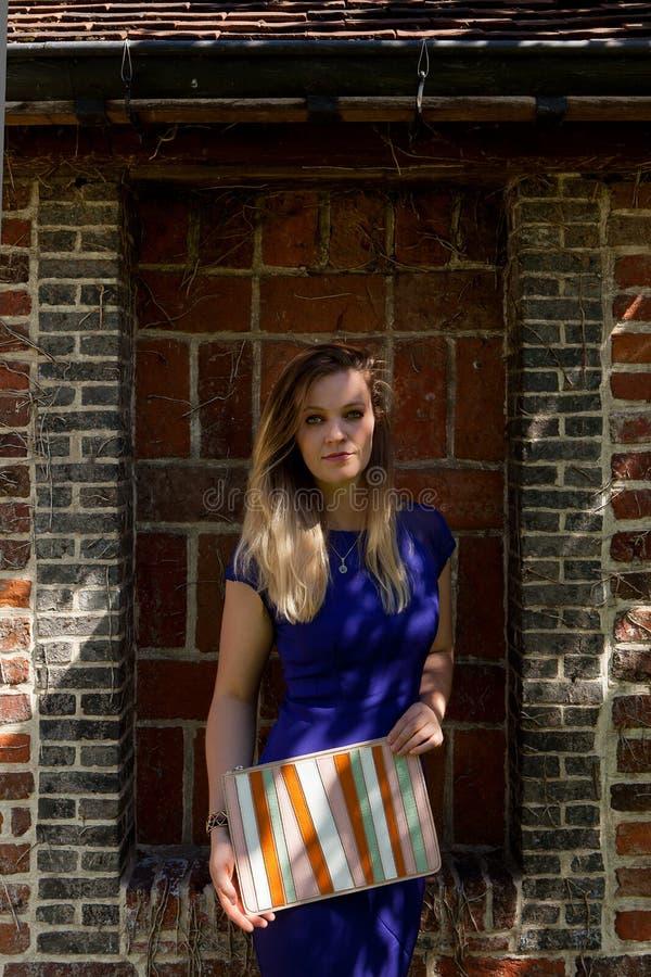 Blonde de zonstraal van de vrouwen blauwe kleding, Groot Begijnhof, Leuven, België stock foto's