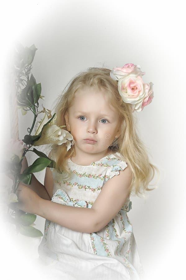 blonde del niño de la niña con las rosas en su pelo fotos de archivo libres de regalías
