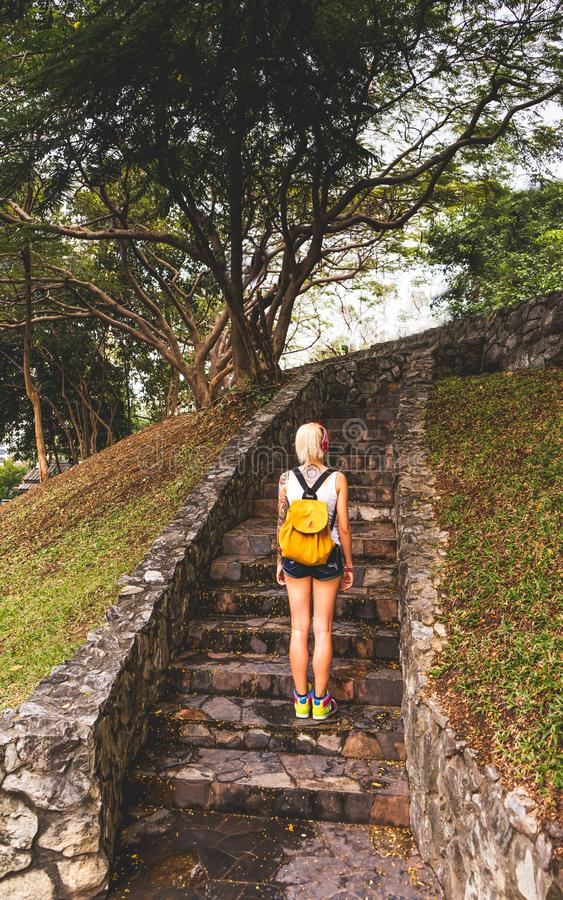 Blonde in denim shorts standing in the park on the stone steps. Wearing white jersey, orange backpack. Hands with. Tattoos. Asia travel royalty free stock photo