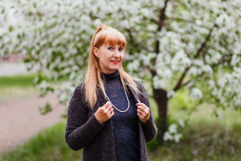 Blonde die mooie vrouw op middelbare leeftijd in het Park in de lente op de achtergrond van bloeiende Apple-bomen glimlachen royalty-vrije stock afbeelding