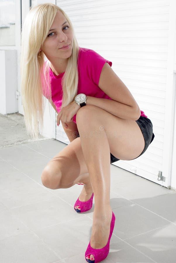 Blonde die op wit hurkt stock fotografie