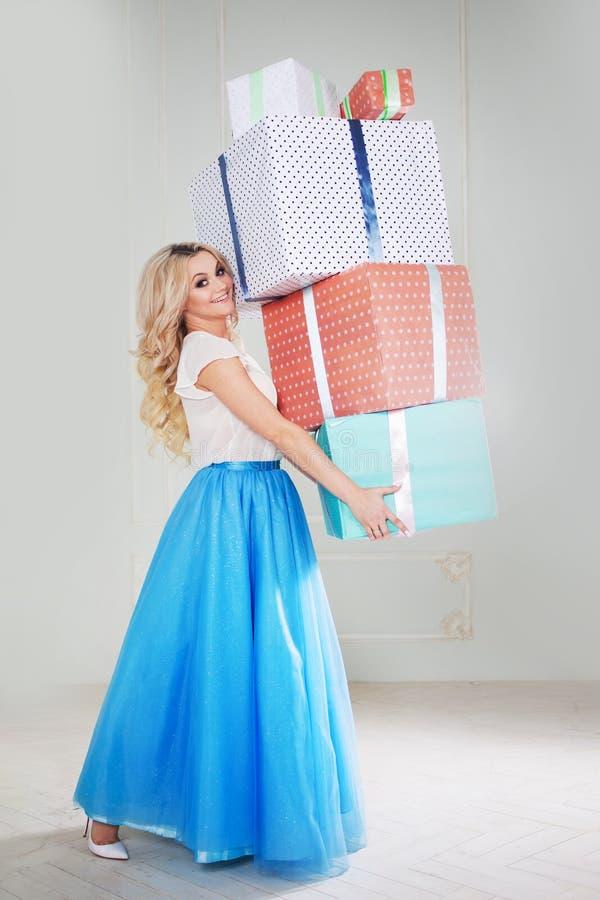 Blonde divertido y hermoso con un manojo de cajas de regalo grandes Mujer joven encantadora en una falda azul curvy fotos de archivo libres de regalías