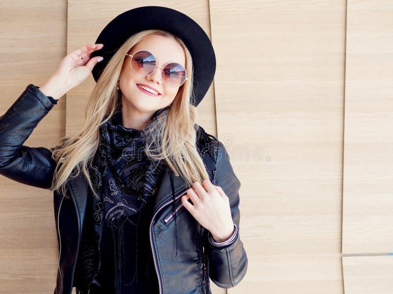 Blonde divertido y hermoso en vidrios de sol y un sombrero Retrato de moda de la muchacha al aire libre Sostiene el sombrero imagen de archivo libre de regalías