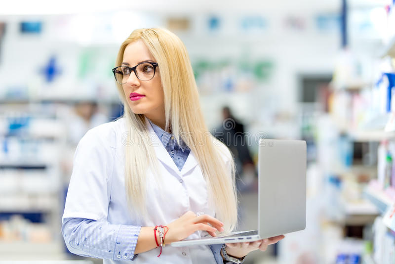 Blonde doctor, young pharmacist searching for prescription drugs on laptop. Pharmacy woman using modern technology stock images