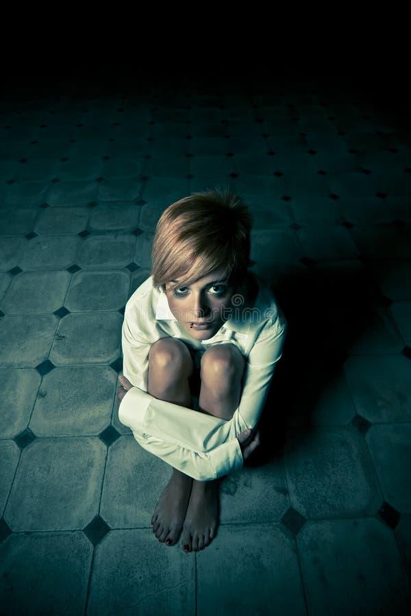 Blonde in duisternis royalty-vrije stock afbeeldingen