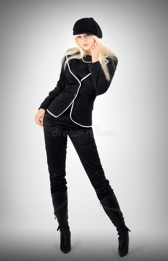 Blonde in een donker kostuum stock foto