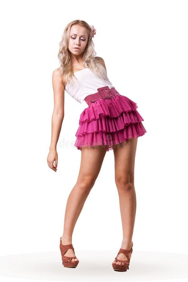 Blonde in een korte roze rok stock foto