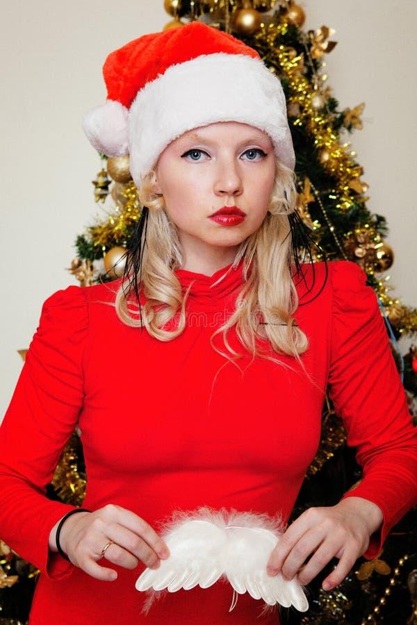 Blonde in een een rode kleding, hoed van het nieuwe jaar en witte engelenvleugels in de handen dichtbij de Kerstboom royalty-vrije stock afbeelding