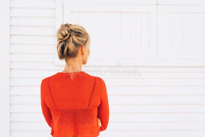 Blonde in een rode sweater stock afbeeldingen