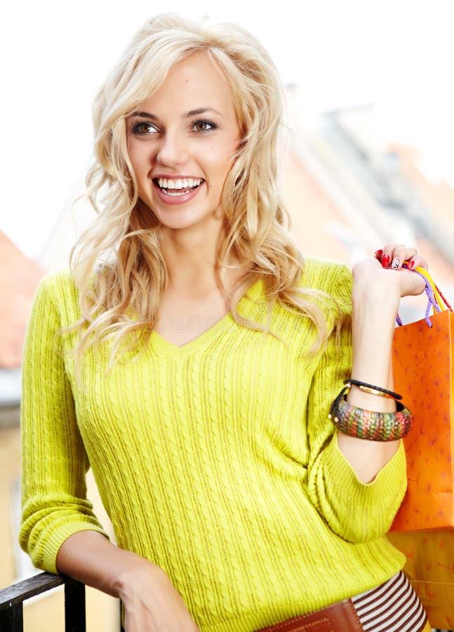 Blonde Einkaufenfrau mit Beuteln stockfoto