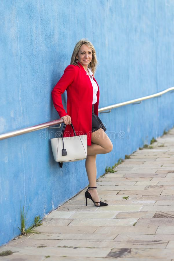 Free Blonde Elegant Woman Wearing Red Jacket Leaning On A Metallic Fence On A Wall Royalty Free Stock Photos - 159094738