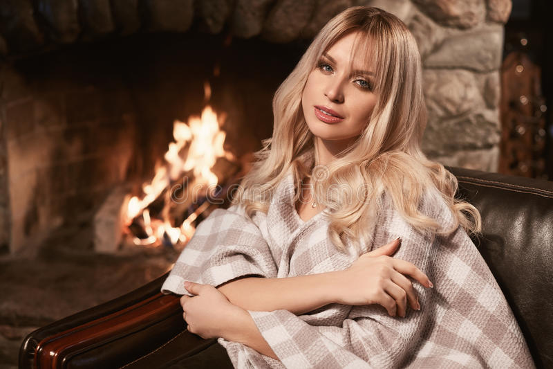 Blonde elegante de Georgeous debajo de la tela escocesa brillante cerca de la chimenea foto de archivo libre de regalías