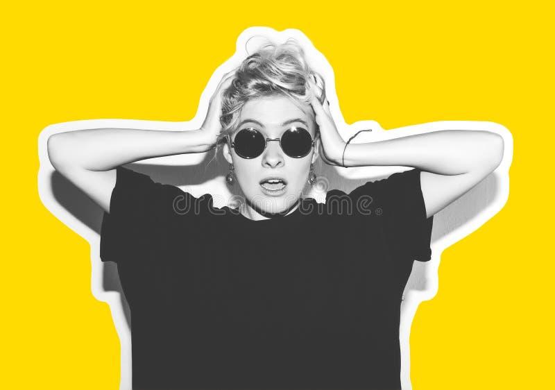 Blonde elegante de la moda con collage colorido del pelo corto La muchacha loca en una camiseta negra y gafas de sol de la roca g imágenes de archivo libres de regalías