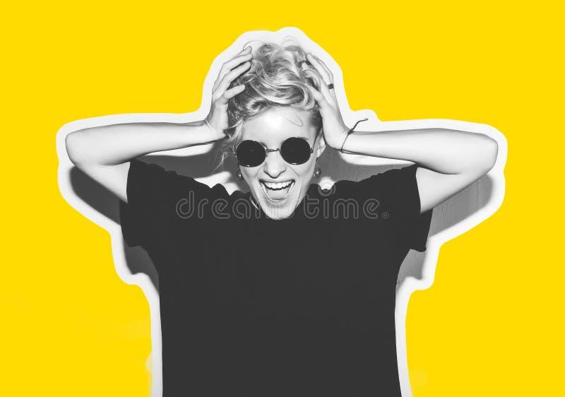Blonde elegante de la moda con collage colorido del pelo corto La muchacha loca en una camiseta negra y gafas de sol de la roca g imagen de archivo