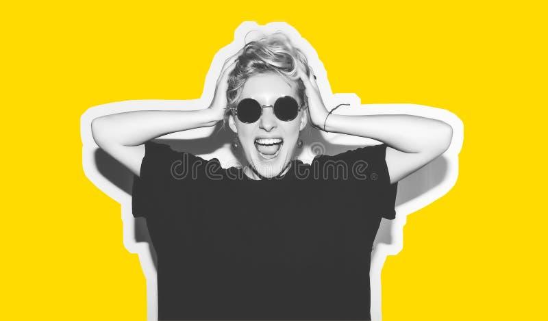 Blonde elegante de la moda con collage colorido del pelo corto La muchacha loca en una camiseta negra y gafas de sol de la roca g stock de ilustración