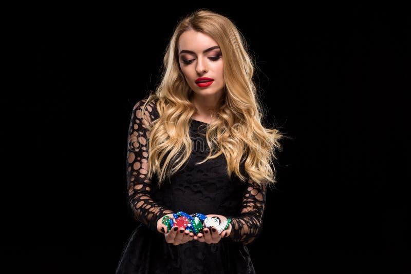 Blonde elegante en un vestido negro, jugador del casino que celebra un puñado de microprocesadores en fondo negro imagen de archivo libre de regalías