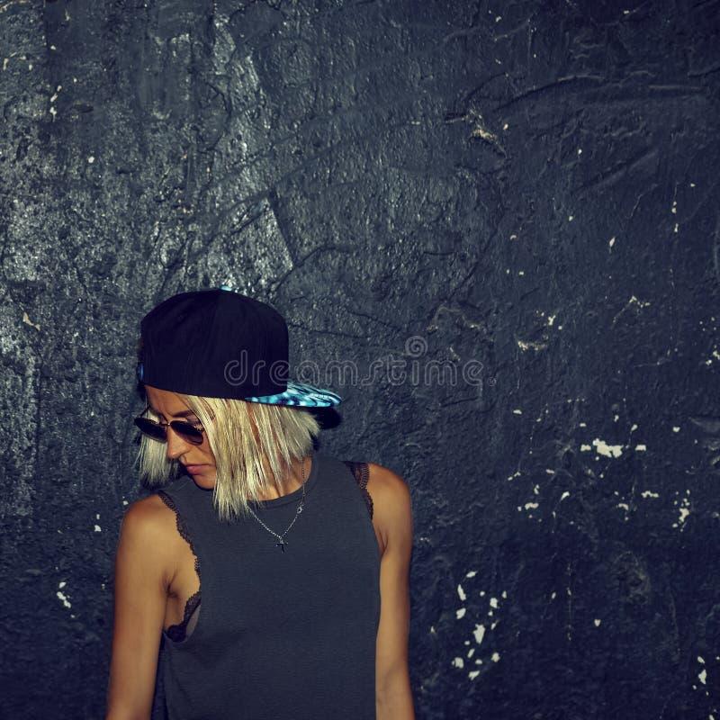 Blonde elegante en vidrios de moda y un casquillo Moda urbana s fotografía de archivo