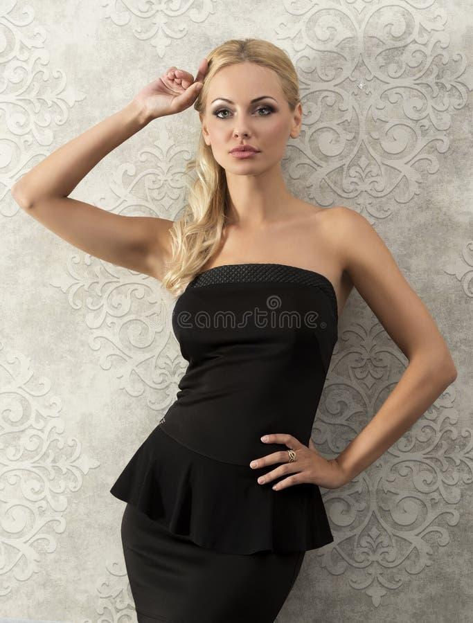Blonde elegante vrouw dichtbij maniermuur stock afbeeldingen
