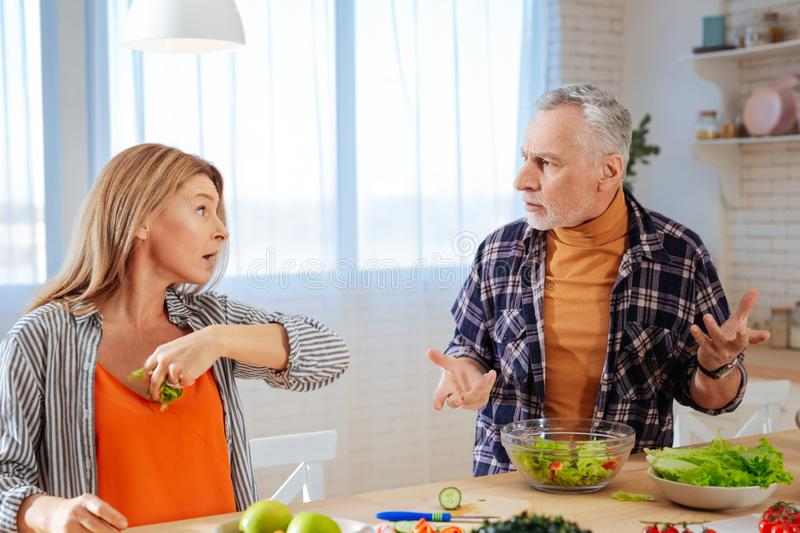 Blonde emotional wife throwing piece of lettuce into her husband. Throwing lettuce. Blonde-haired emotional wife throwing piece of lettuce into her bearded royalty free stock photos